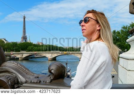 Portrait Of A Pretty Blonde Woman In Town By The Water, Standing On A Beautiful Historic Bridge. Cit