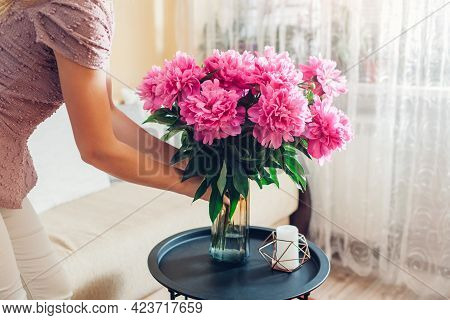 Woman Puts Vase With Bouquet Of Pink Peonies Flowers On Table. Housewife Taking Care Of Coziness At