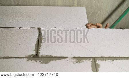 Construction Of A Cinder Block Wall. Block Installation And Erection Of A Wall From A White Block.