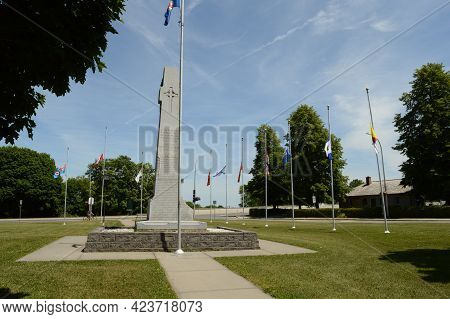 Smiths Falls, Ontario, Ca, June 12, 2021: A Canadian War Memorial Site With The Flags At Half Mass L