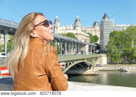 Portrait Of A Beautiful Blonde Woman In Town At The Water's Edge. Bridge And Historic Building Delib