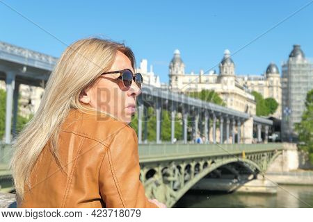 Profile Portrait Of A Blonde Woman In The City Of Paris. Bir Hakeim Bridge And Historic Building Del