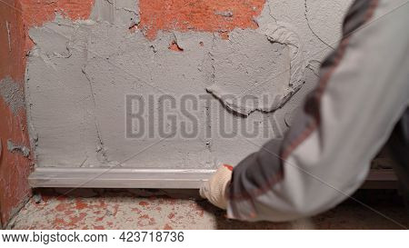 A Worker Uses A Construction Tool To Level Mortar On The Wall. Builders Use Cement Plaster To Level