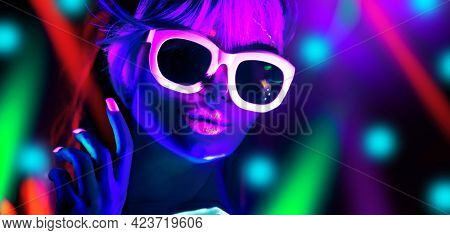 Disco dancer in neon light in night club Fashion model woman in neon light, portrait of beautiful girl with fluorescent make-up, Body Art design in UV, sunglasses, colorful make up.