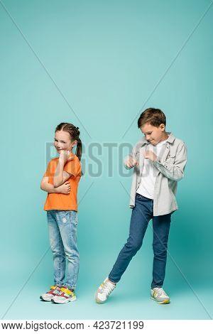 Shy Girl Standing Near Boy Dancing On Blue