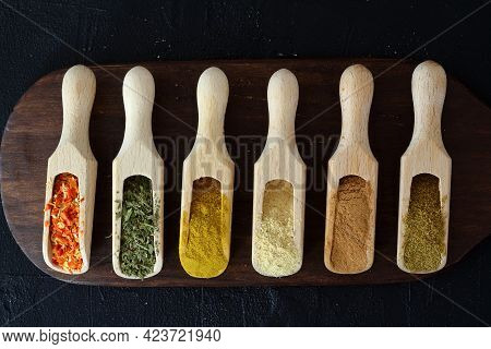 Different Kind Of Spices On A Black Stone. Oriental Spices In Spoons, Red Peppers, Curry Powder, Cin