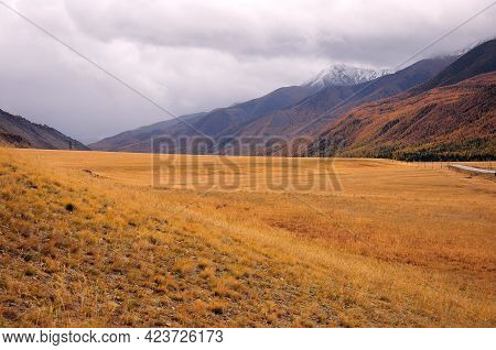 A Narrow Valley In Autumn Surrounded By Mountain Peaks In Thunderclouds.
