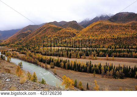 View From The Top Of The Hill To A Picturesque Valley With A Flowing Turquoise River In Early Autumn