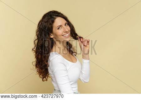 Young Woman With Healthy Long Curly Hair. Portrait Of Happy Brunette Caucasian Female Dressed In Whi
