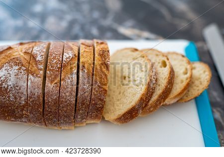 Closeup Of Loaf Of Homemade Artisan Wheat Bread, Partially Sliced, With Crunchy Crust, Open Crumb, W