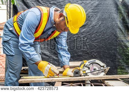 Construction Worker Are Using Tape Measurements To Measure Planks And Pencil Are Used To Write, Male