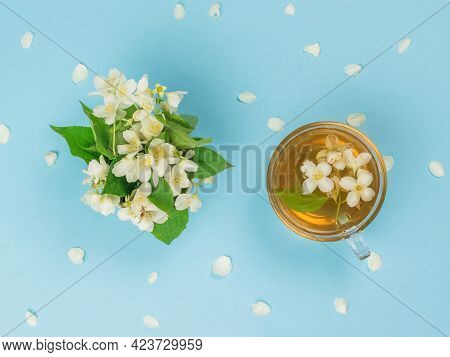 A Cup Of Tea And A Bouquet Of Jasmine On A Blue Background. An Invigorating Drink That Is Good For Y