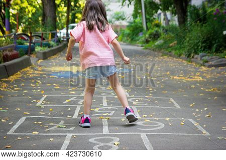 Little Cute Girl 5 Y.o. Playing Hopscotch On Playground Outdoors. Selective Soft Focus