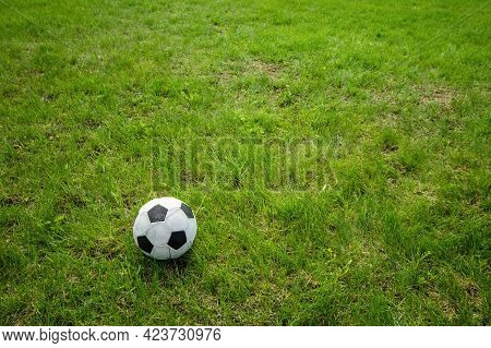 Football Soccer Ball On Green Grass Field With Big Copy Space.