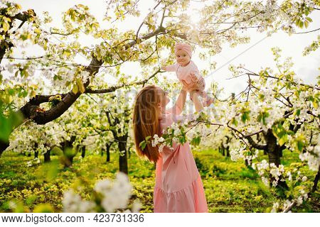 Mother With Baby In Arms In Flowering Garden. Surgery For Child With Cleft Lip.