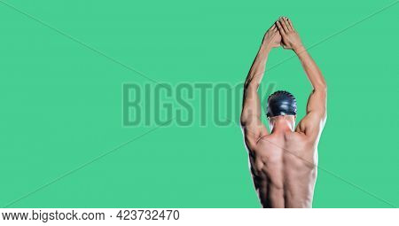 Composition of male swimmer with copy space isolated on green background. sports and competition concept digitally generated image.