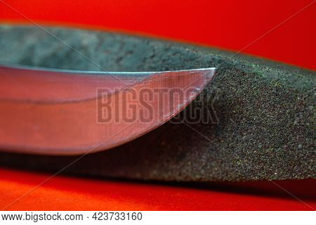 Knife Sharpening And Stone For Sharpening Knives On A Red Background