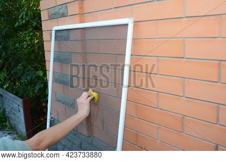 Cleaning A Window Mosquito Net Before Installing An Insect Mosquito Screen On A Window.