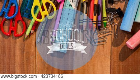Composition of text school deals in white on blue circle, with school stationery on wooden desk. school, education and study concept digitally generated image.