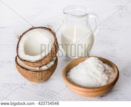 Coconut Milk With Coconut Chips And Broken Coconut On A White Textured Background