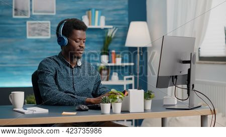 African American Black Manager Using Headphones To Listen Music While Working From Home Office On Co