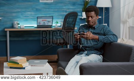 Exhausted African American Man Falling Asleep While Holding Phone In His Hands, Overworked Manager O