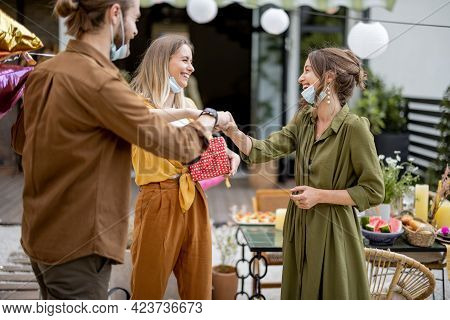 Young Adult Friends Gathering For Birthday Party At The Backyard Of Country House. Wearing Face Mask