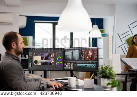 Videographer Editing, Cuting Footage And Sound On Computer With Dual Monitors Setup Working In Creat
