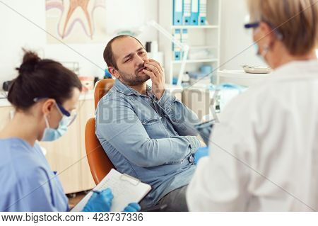 Sick Patient With Toothache Speaking With Stomatologist Showing Affected Mass. Man Explaining Dental