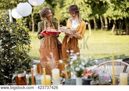 Friends Preparing For The Festive Dinner, Two Housewifes Carrying Hot Meal And Serving The Table. A