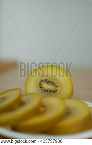 Slices Of Golden Kiwi With Yellow Pulp On White Plate On The Kitchen. Exotic Fruits, Healthy Eating