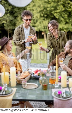 A Group Of Young Friends Have Delicious Dinner, Toasting And Having Great Summertime Together At The