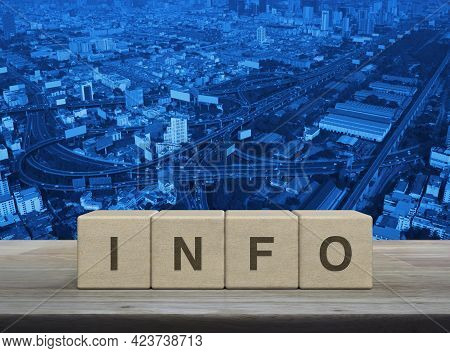 Info Letter On Block Cubes On Wooden Table Over Modern City Tower, Street, Expressway And Skyscraper