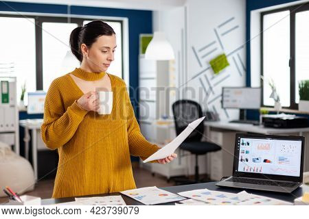 Confident Business Woman Holding Documents With Statistics Enjoying A Cup Of Coffee. Executive Entre
