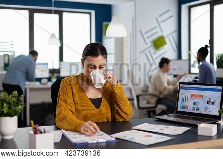 Brand Manager Businesswoman Drinking A Cup Of Coffee Analysing Financial Start Up Charts. Executive