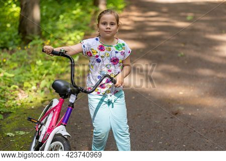 A Child Girl Learns To Ride Bike In A Park. Portrait Of A Cute Girl On Bicycle.