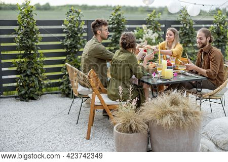 A Group Of Young Friends Have Delicious Dinner, Having Great Summertime Together At The Backyard Of
