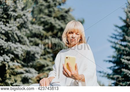 Mature Adult Woman Having A Selfie And Taking Funny Grimace With Cellphone. Happy And Smiling Senior