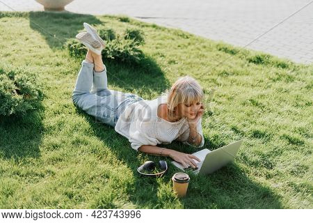 Mature Adult Woman Using Laptop, Lying On The Grass Outdoors In Summer Park. Happy And Smiling Senio