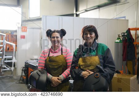 portrait of two welders holding welding masks in their hands and preparing for hard work in a factory