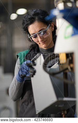 Woman worker wearing safety goggles control lathe machine to drill components. Metal lathe industrial manufacturing factory