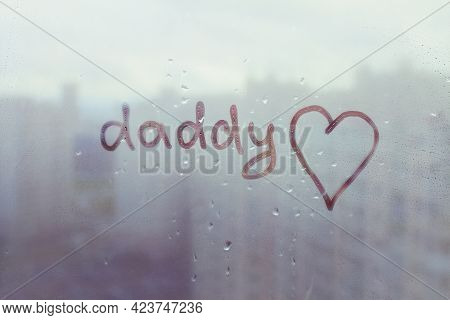 Handwritten Word Daddy And Hand Drawn Heart By Child On Misted Sunset Orange Window With Raindrops A