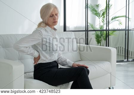 An Elderly Woman Suffering From Back Pain. A Middle-aged Woman Gets Up From The Sofa And Experiences