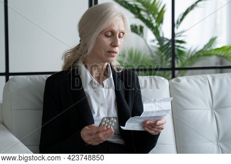 Gray Haired Elderly Woman Reads The Instructions Before Taking Her Medication At Home. Grandmother S