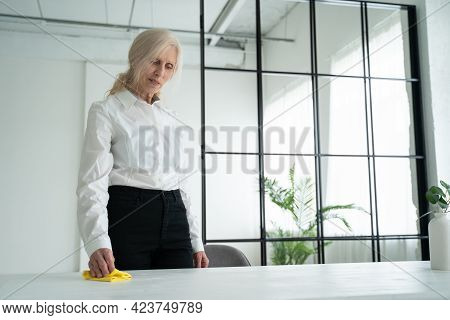Mature Woman Wipes A Wooden Table With A Rag. Elderly Woman Smiling And Wipe Away Dust