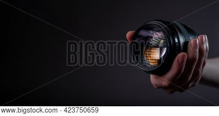 Modern Digital Camera Lense 85 Mm In Hand Over Dark Black Grey Background With Place For Text.
