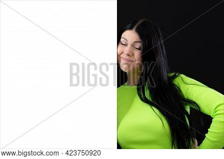 Attractive Dark-haired Woman In Bright Colored Clothes With A White Blank Poster, Isolated On A Dark