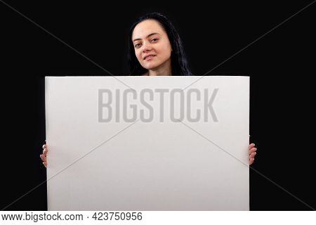 Attractive Dark-haired Woman In A Gray Sweater With A White Blank Poster, Isolated On A Dark Backgro