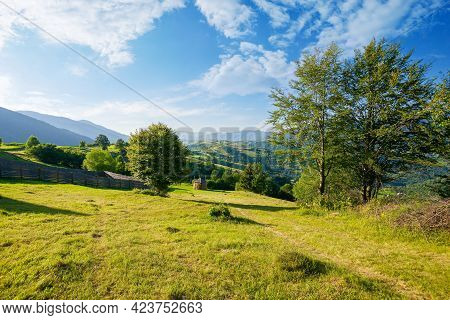 Mountainous Rural Landscape. Trees On Hills And Grassy Fields Rolling In To The Distant Ridge Beneat