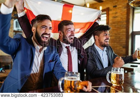 People, Leisure, Friendship, Sport Concept. Happy Friends Drinking Beer, Watching Sport Game At Pub
